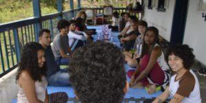 Imagem mostra, em primeiro plano, mergulhador Felipe Carvalho, ministrando treinamento para membros da equipe do Projeto Manuelzão, que estão em segundo plano. Todos estão sentados no chão, formando duas filas, uma de frente para a outra..