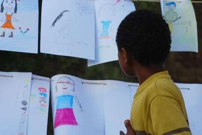 Criança observando exposição de desenhos realizada durante a Expedição pelo Velhas 2009: encontros de um povo com sua bacia (Foto: Marcelo Andrê/acervo Projeto Manuelzão)